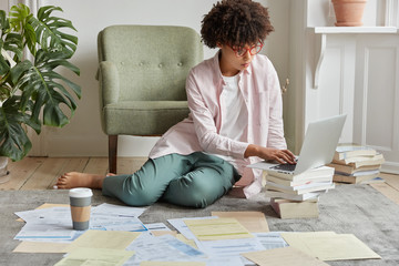 Serious black young female administrative manager thinks over successful strategy of entrepreneurship, uses scientific literature and works with paper documents, poses on floor in apartment.
