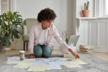 Indoor shot of busy young woman dressed in casual clothes, sits on floor with paper documents, prepares business project, wears transparent glasses, drinks takeaway coffee. Domestic interior