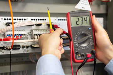 Electrician measurements with multimeter tester. Male Technician Examining Fusebox