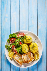 Wall Murals Ready meals Fried fish with potatoes on wooden table