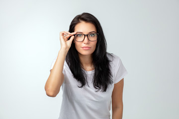 Shocked pretty woman touching her glasses and looking at the camera, surprised female staring at the camera isolated on the white background.