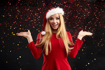 Beautiful smiling woman with long blond hair in Santa hat and red dress looking at camera with spreaded hands enjoying sparkles over black background. Christmas and New Year Concept