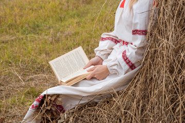 Beautiful girl in a Slavic dress reads a book at a haystack in autumn
