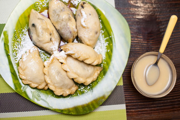 Vegetarian dumplings with berries and with poppy seed on a green plate. Along with the plate is a vanilla sauce in a saucepan
