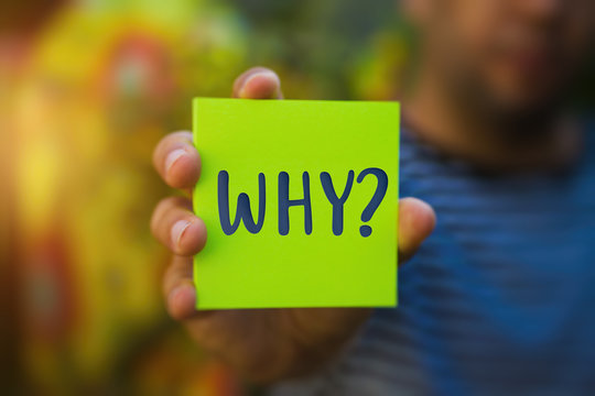 Hand holding a green Paper with the word why against blurred background - Why?, Business Concept