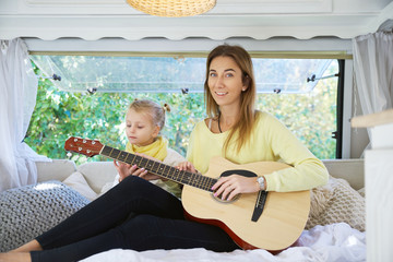 Attractive smiling woman playing guitar sitting on the bed and her little daughter is interested in watching the process. The concept of travel, entertainment, life in a mobile home