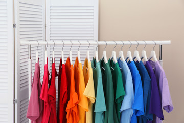 Rack with bright clothes in room. Rainbow colors