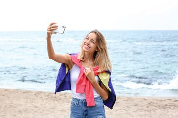 Attractive woman taking selfie on sea coast