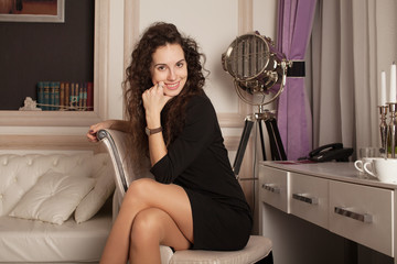 Beautiful woman in a black dress in a armchair in hotel room