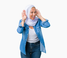 Middle age eastern arab woman wearing arabian hijab over isolated background Trying to hear both hands on ear gesture, curious for gossip. Hearing problem, deaf