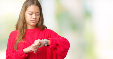 Young beautiful brunette woman wearing red winter sweater over isolated background Checking the time on wrist watch, relaxed and confident