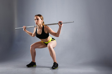 Beautiful and strong young woman doing sit-ups with a barbell for growth of buttocks. Concept of powerlifting and training hall. Copyspace