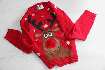 Warm Christmas sweater on white wooden background. Seasonal clothing