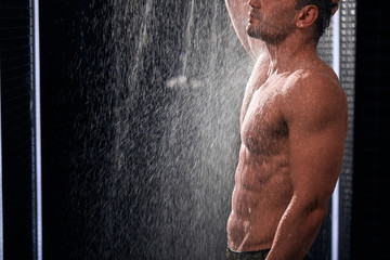 Inrecognizable athletic man with muscular body washing stress away under running water in shower room. Close up portrait of young musclar man washing his perfect body with water drops. Wall mural