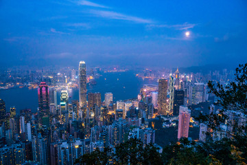 Full moon rise over Hong Kong Skyline at dusk. Modern China city with skyscrapers near the ocean