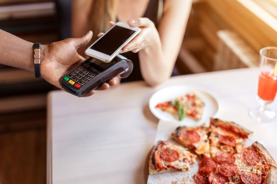 Blonde Female customer paying with NFC technology on smart phone for her dinner.