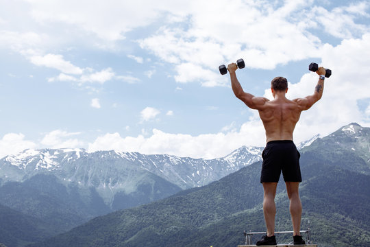 Young and sporty muscular half naked crossfit male athlete training with dumbbells outdoor over green mountains and blue sky background. Sport, health, outdoor athletics.