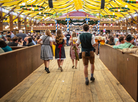 Oktoberfest, Munich, Germany. Waiter holding beers, tent interior background