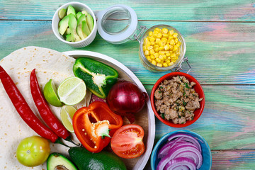 Ingredients for Burritos wraps meat, corn, tomatoes and peppers on wooden background. Top view