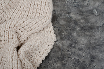 Woolen scarf on the gray marble or concrete background (as a contrast of two different textures and backgrounds)