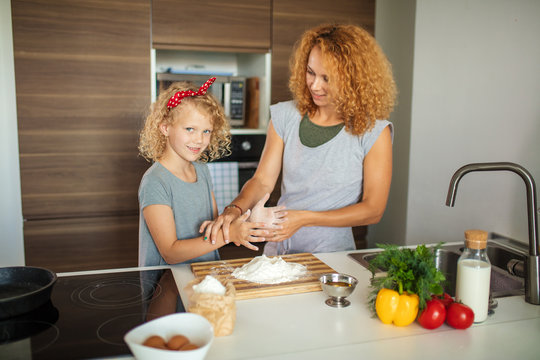 Happy attractive woman with her seven years old kid girl cooking holiday pie in the kitchen to Mothers day, casual lifestyle in real life interior, everyday life