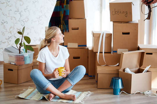 smiling woman with tea in hand sitting on floor of new apartment, pile of moving boxes on background