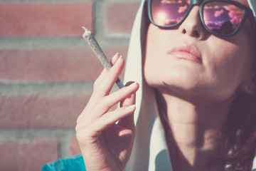 Young woman with weed joint. Marijuana and cannabis legalisation concept.
