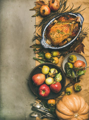 Thanksgiving dinner table. Flat-lay of roasted chicken or turkey, fruit, pumpkin, cutlery, leaves over yellow linen table runner on grey concrete background, top view, copy space, vertical composition