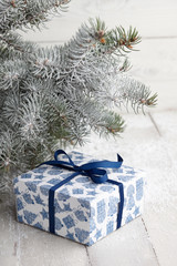 Christmas blue gift box with festive pattern under snowy fir tree