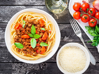 pasta bolognese with tomato sauce, ground minced beef, basil leaves on dark rustic wooden table, top view