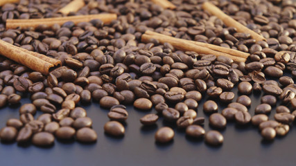 Placer coffee beans and cinnamon sticks on a dark background