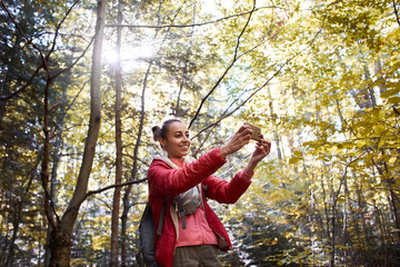 happy smiling woman in a red jacket walking in the autumn forest