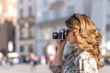 Vacation photographer concept - beautiful and attractive woman holding a retro SLR camera and shooting famous landmarks of a historic city (copy space)