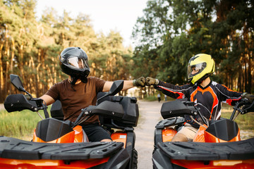 Poster Motorise Two atv riders hits fists for good luck, back view