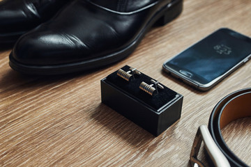 Different men's accessories such as: shoes, belt,  cufflinks and telephone - are on the table