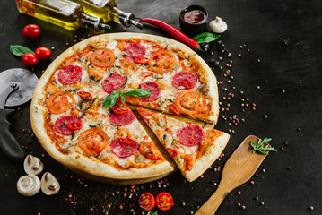Tasty pizza with salami and cheese on black background