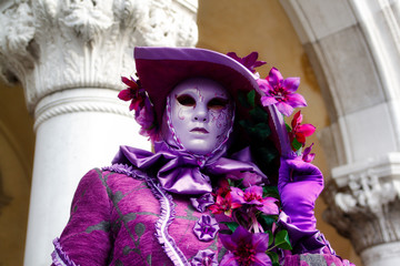 Colorful carnival pink-lilac mask and costume at the traditional festival in Venice, Italy