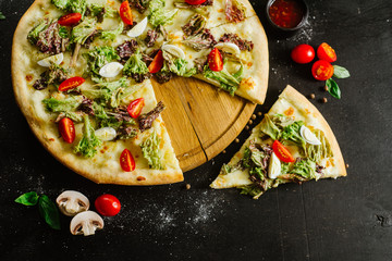 A vegeterian pizza withvagetables and herbs on black background