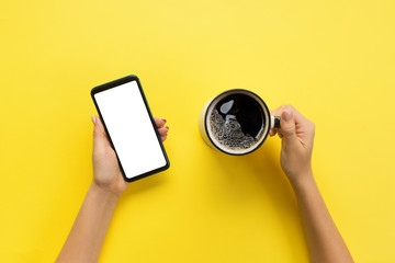 Female hands holding black mobile phone with blank white screen and mug of coffee. Mockup image with copy space. Top view on yellow background, flat lay