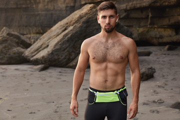 Waist up shot of bodybuilder being in good physical shape, looks directly at camera, has beard, uses wireless earphones for listening radio, has jogging on seashore, serious look. Lifestyle concept