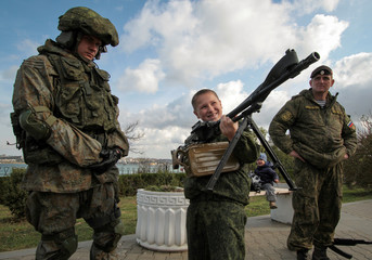 """A boy holds a machine gun at a military hardware exhibition during a swear-in ceremony for new recruits of the Russian military-patriotic club """"Yunarmia"""" (Young army) in the Black Sea port of Sevastopol"""
