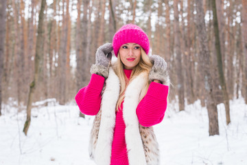 Fashion and people concept - Attractive young woman standing in pink warm jacket in winter snowy park