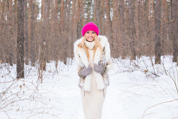 Nature, fashion and people concept - Young attractive blond woman posing in the winter park.
