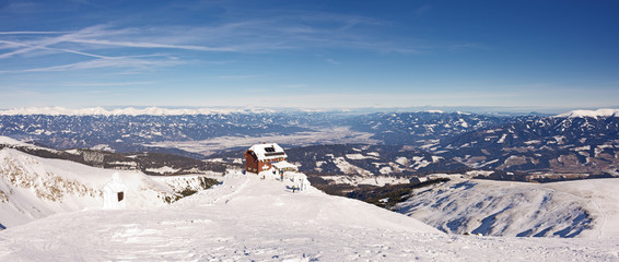 Picturesque winter landscape panorama with high snowy mountains and alpine hut under sunny skies. Panoramic view from top of Styrian mountain Zirbitzkogel, Steiermark, Austria.