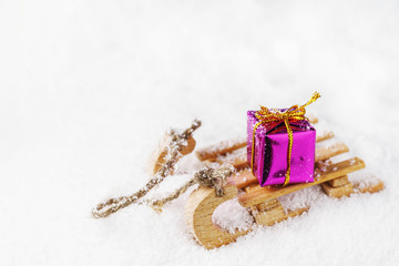 Wooden sleigh with Christmas present on snow with copy space