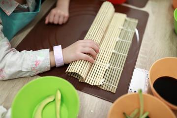 Child preparing sushi rolls