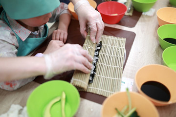 Kid rolling mat over sushi