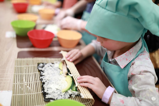 Child rolling mat over sushi