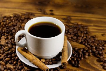 Cup of coffee, roasted coffee beans and cinnamon sticks on wooden table