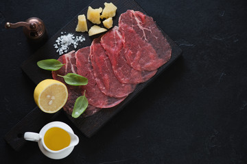 Carpaccio made of raw marbled beef over black stone background, high angle view, horizontal shot with copyspace